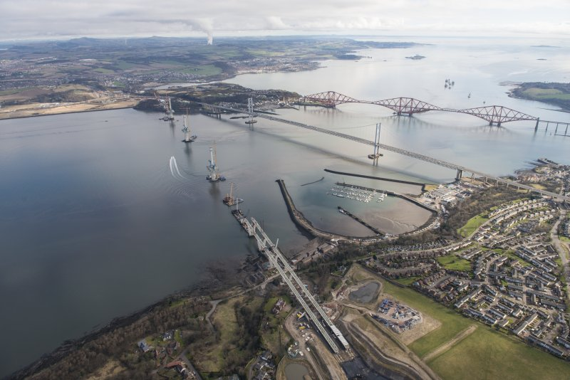 Oblique aerial view of the construction of the Queensferry Crossing with the Forth Road Bridge and the Forth Bridge beyond, looking NE.