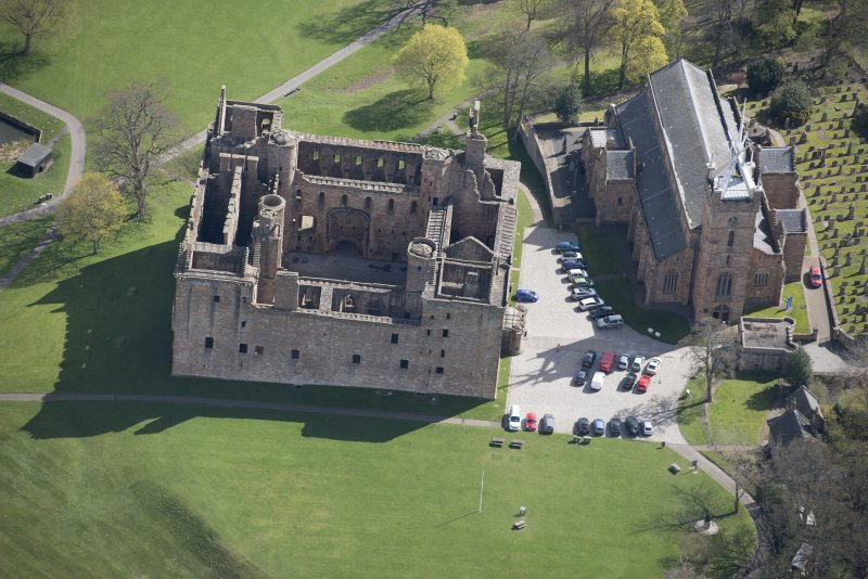 Oblique aerial view of Linlithgow Palace and St Michael's Church, looking E.