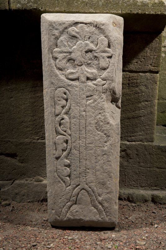 Obliquely lit view of medieval cross slab.