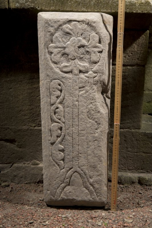Obliquely lit view of medieval cross slab (with scale).