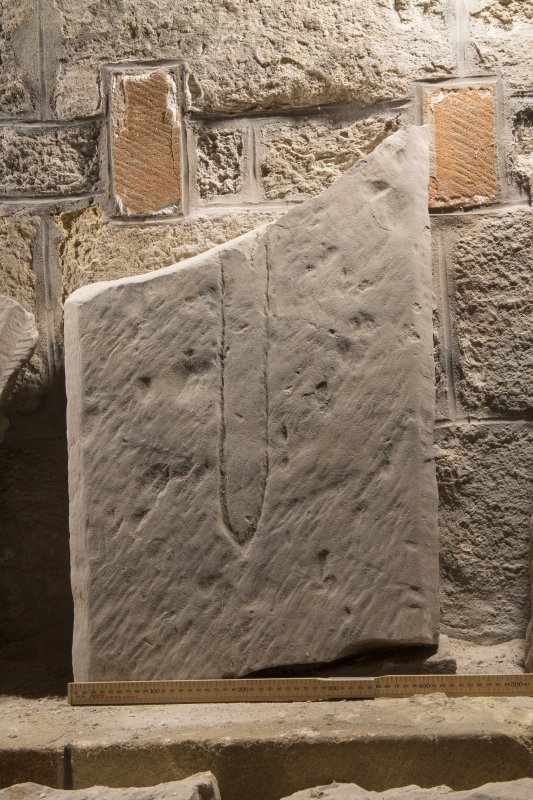 Obliquely lit view of medieval cross slab fragment (with scale).