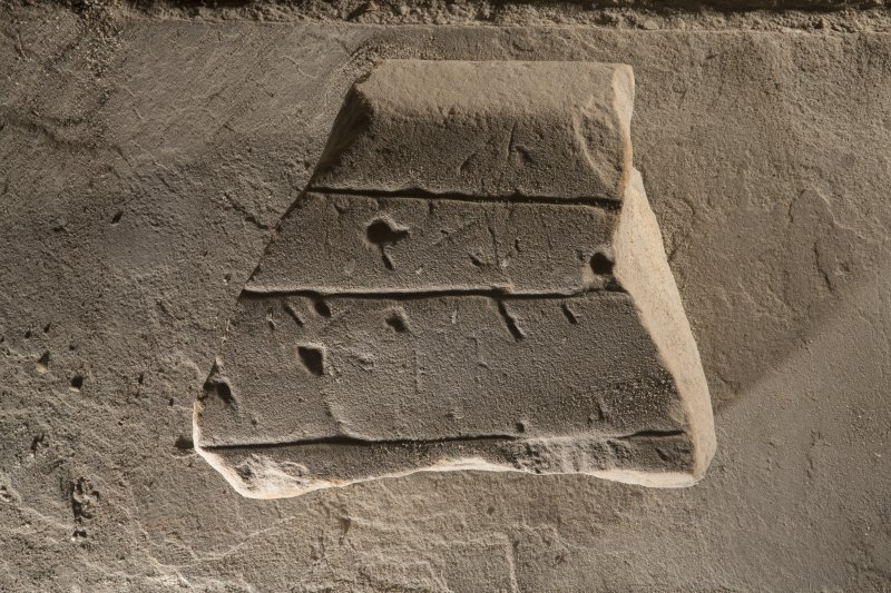 Obliquely lit view of medieval cross slab fragment.