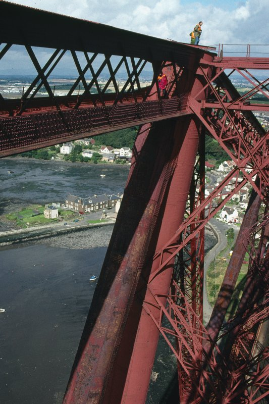 Forth Bridge:  Detailed view within the top area of the Fife Cantilever, with North Queensferry below, and the Forth Bridge Inspector standing on top of the cantilever for scale