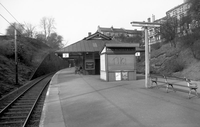 View from SW showing part of SSW front of platform building with newsagent building in foreground