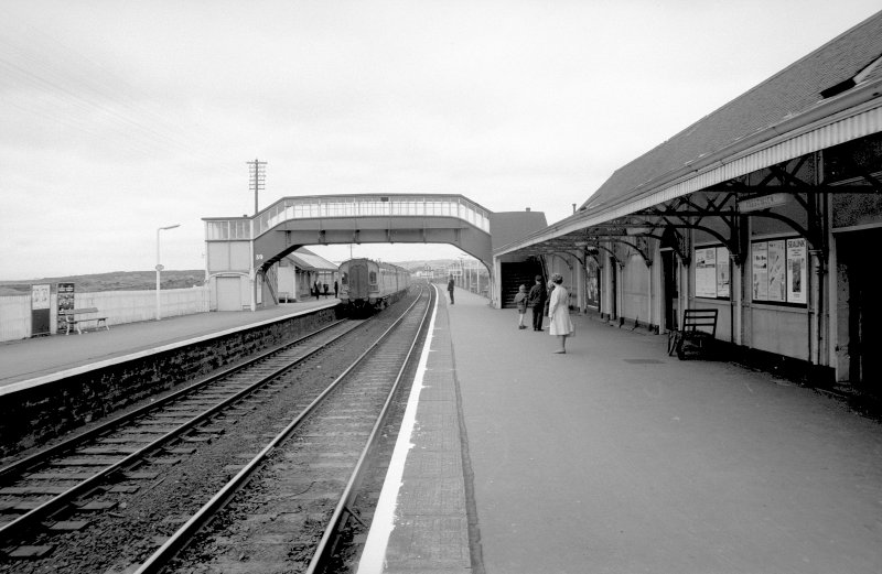 Scanned image of view looking NNE showing SSW front of footbridge with up platform building in background and part of down platform building on right
