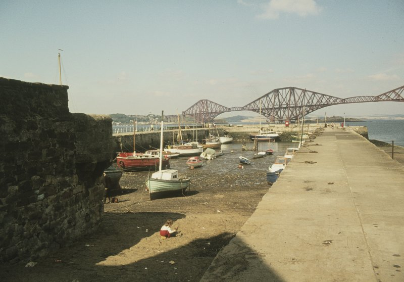 General view from SSW showing boats moored in harbour at low tide with Forth Bridge in background