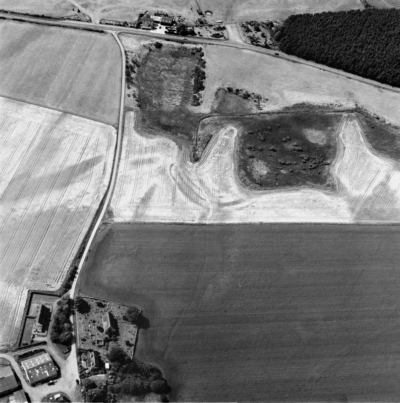Gilchrist, oblique aerial view, taken from the E, centred on the cropmarks of a promontory fort. Kilchrist Church is visible in the bottom left-hand corner of the photograph.