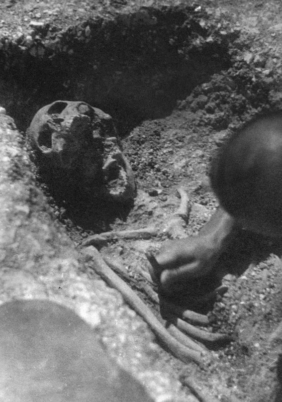 Digital copy of excavation photograph showing excavation of a single inhumation.