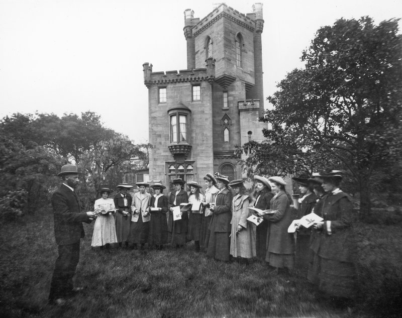 View of group outside St John the Baptist's Church, Ayr. Titled on mount: 'Mr Alexander, S Alexander with students from Ayr Academy. Before Restoration by marquis of Bute 1914'.