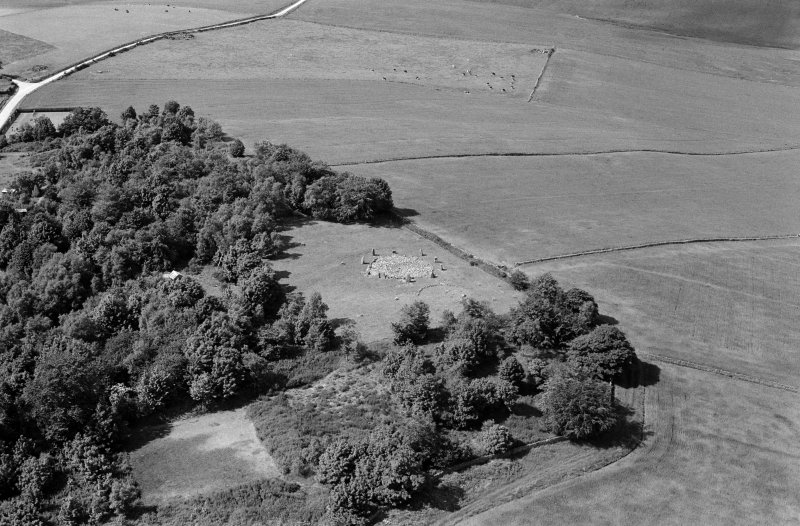 Oblique aerial view centred on the remains of the stone circle and enclosed cremation cemetery at Loanhead of Daviot, looking to the NW.