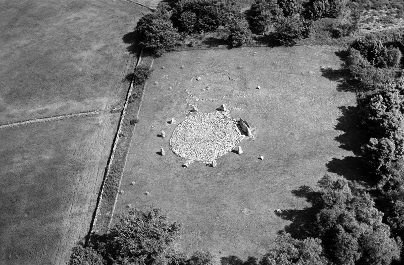 Oblique aerial view centred on the remains of the stone circle and enclosed cremation cemetery at Loanhead of Daviot, looking to the ESE.