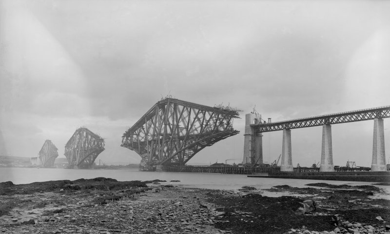 View of the Forth Bridge under construction seen from the South from the slipway.