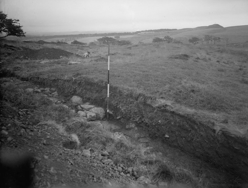Cairnpapple Hill, photograph of excavation showing cutting through henge bank on W side.