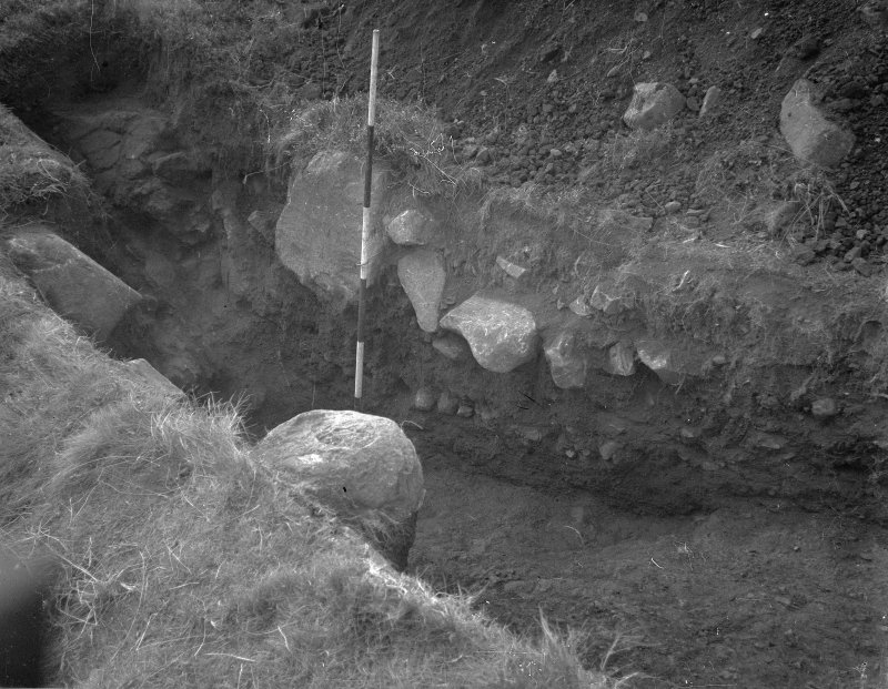 Cairnpapple Hill, photograph of excavation showing henge ditch on W, section X with kerb stone of Period IV cairn.