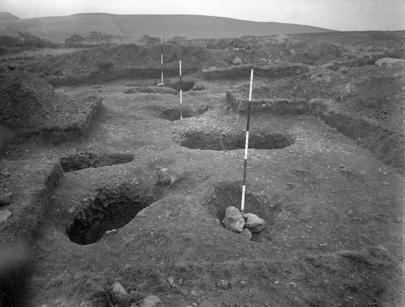 Cairnpapple Hill, photograph of excavation showing stone-holes 6 to 8 (with ranging rods), Beaker grave and Inhumation graves 1-4.