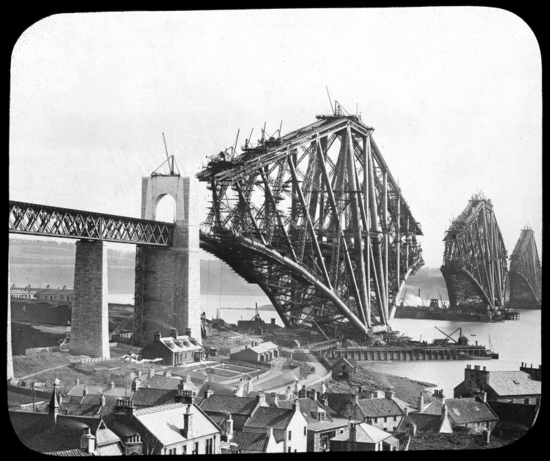 View of the bridge under construction seen from North Queensferry. Insc. 'Progress of Work. Registered G.W.W. Trade Mark.' Lantern slide.