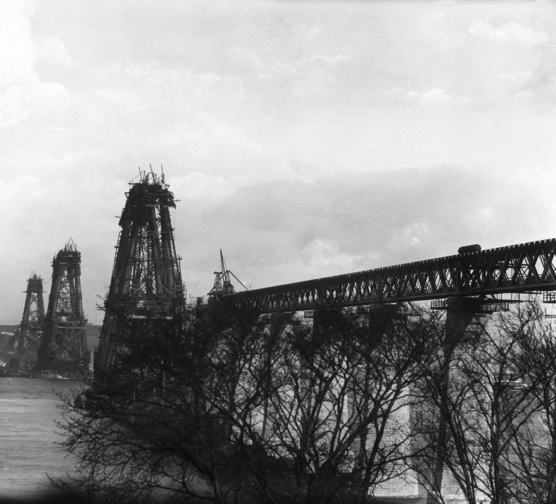 View of the North cantilever of the Fife erection under construction seen from the North Queensferry shore. Insc. 'N. Cantilever.  F. Bridge.  C. Cameron.' Lantern slide.
