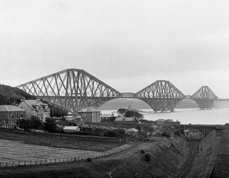 View of the bridge from the North West with houses and fields in the foreground. Insc. 'Forth Bridge from N.W. Co. Cameron.' Lantern slide.