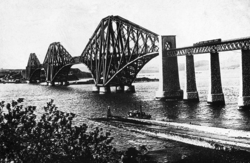 General view of the bridge in use seen from the South West. Insc. on negative 'The Forth Bridge. Length 8296 Ft. Height 354 Ft. Spans 1700 Ft each. J. Patrick.' Insc. on front of mount 'Forth Bridge & Hawes Pier.' Insc. on back of mount 'T.J. Walls, Optician, 12 Forrest Road., Edinr.' Lantern slide.