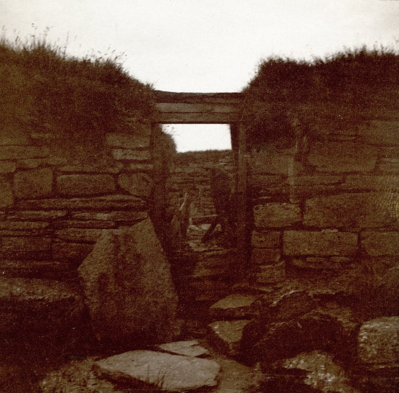 Photograph of part of a Broch, stones, wooden props and vegetation