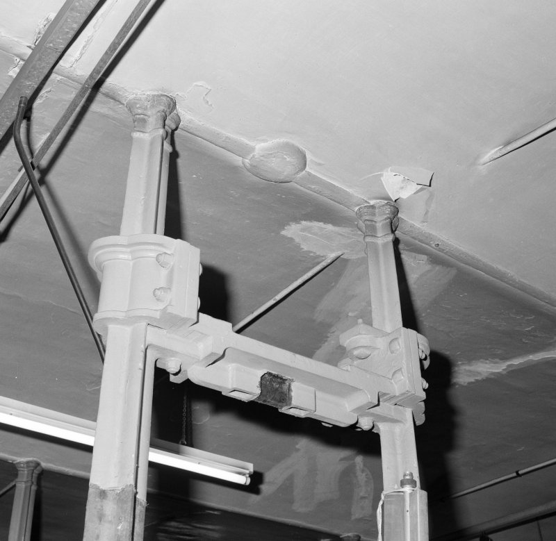 Interior.  Detail of cast iron columns at ceiling level on ground floor.