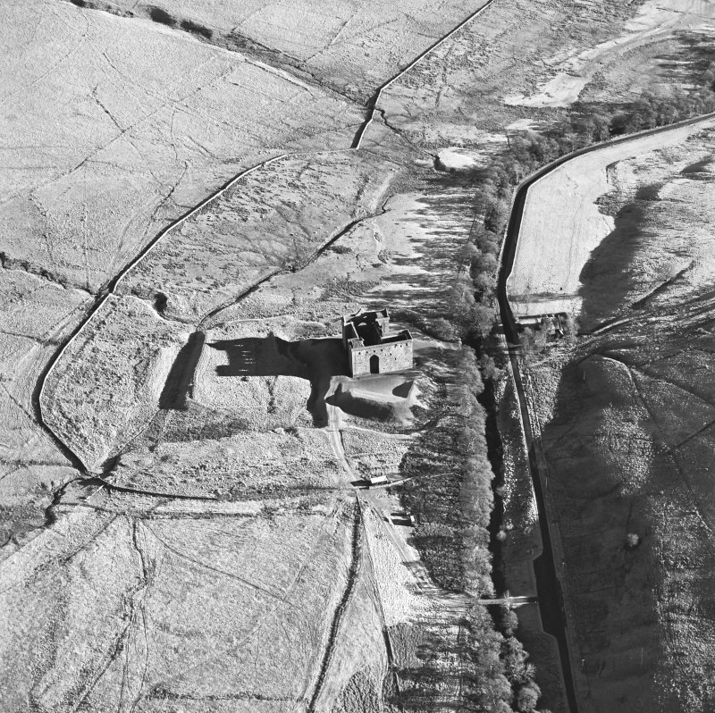 Oblique aerial view of Hermitage Castle centred on the remains of a castle, taken from the W.
