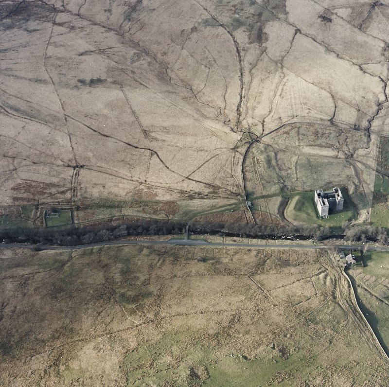 Oblique aerial view centred on the remains of the castle, chapel and moated site, taken from the S.