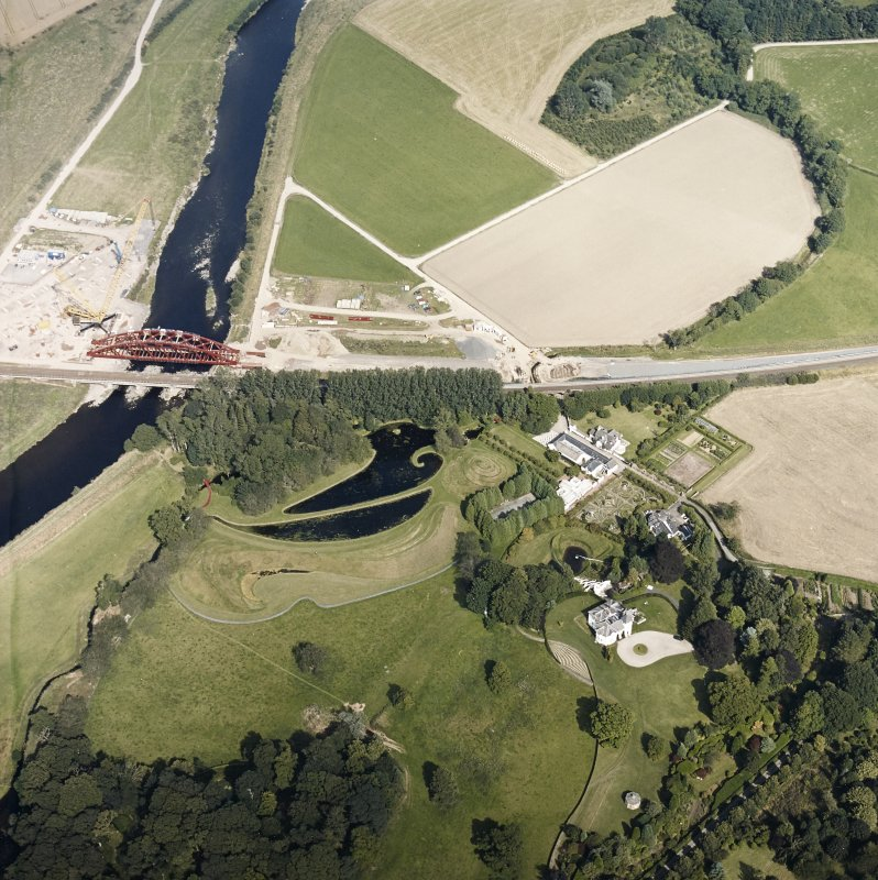 Oblique aerial view centred on the country house and garden with the lodge, railway viaduct and construction works adjacent, taken from the WSW.