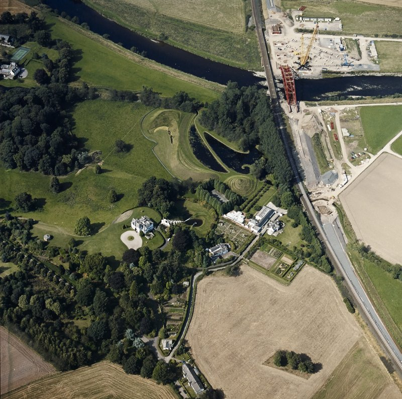 Oblique aerial view centred on the country house and garden with the lodge, railway viaduct and construction works adjacent, taken from the S.