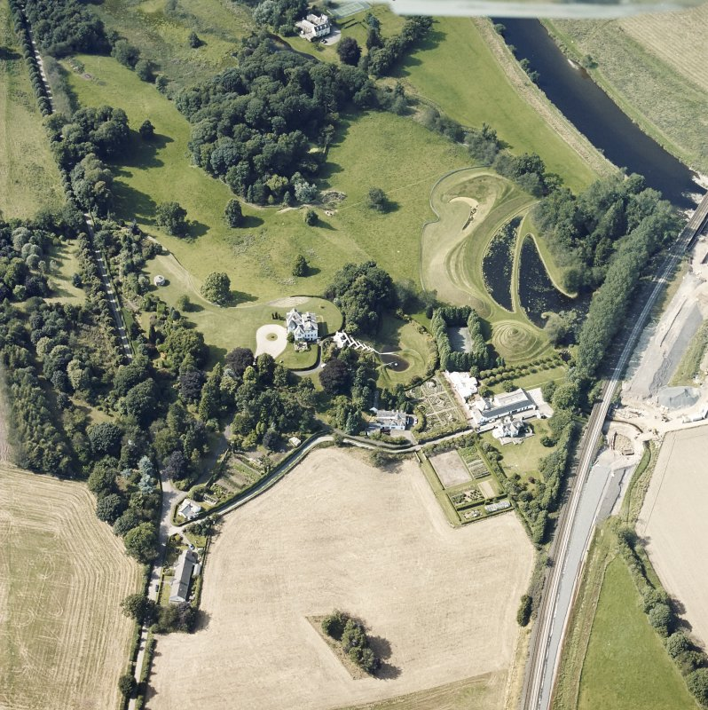 Oblique aerial view centred on the country house and garden with the lodge adjacent, taken from the SE.