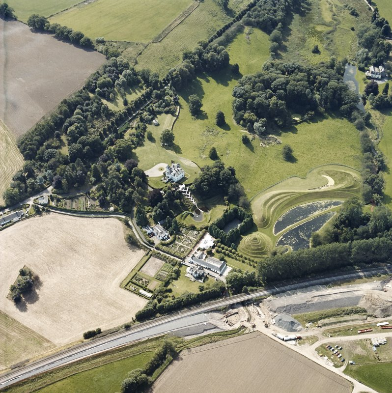 Oblique aerial view centred on the country house and garden with the lodge adjacent, taken from the ENE.
