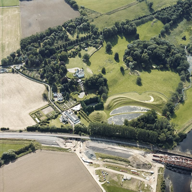 Oblique aerial view centred on the country house and garden with the lodge, railway viaduct and construction works adjacent, taken from the NE.