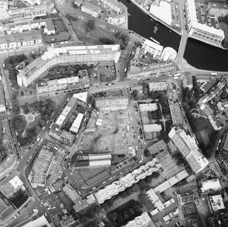 Oblique aerial view centred on the excavation with the warehouses and offices adjacent, taken from the SE.
