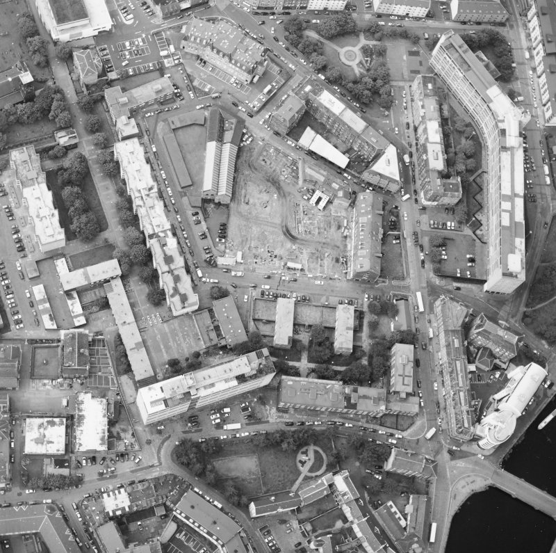 Oblique aerial view centred on the excavation with the warehouses and offices adjacent, taken from the NE.