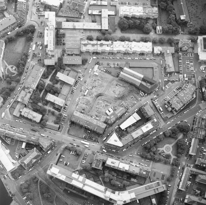 Oblique aerial view centred on the excavation with the warehouses and offices adjacent, taken from the NW.