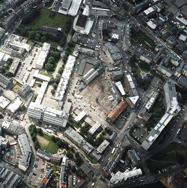 Oblique aerial view centred on the excavation with the warehouses and offices adjacent, taken from the N.