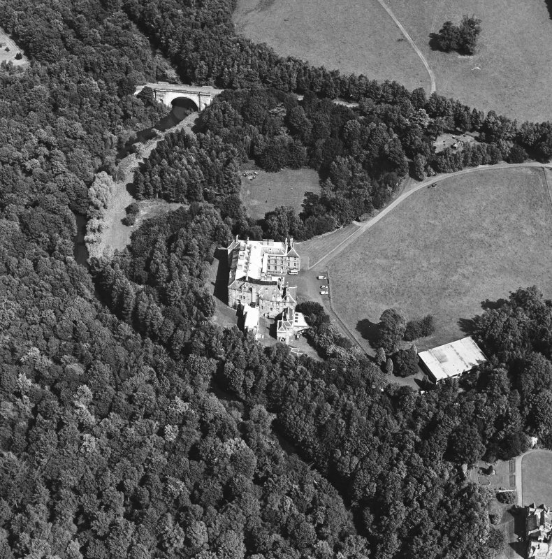 Oblique aerial view centred on the country house and garden with bridge adjacent, taken from the SSW.