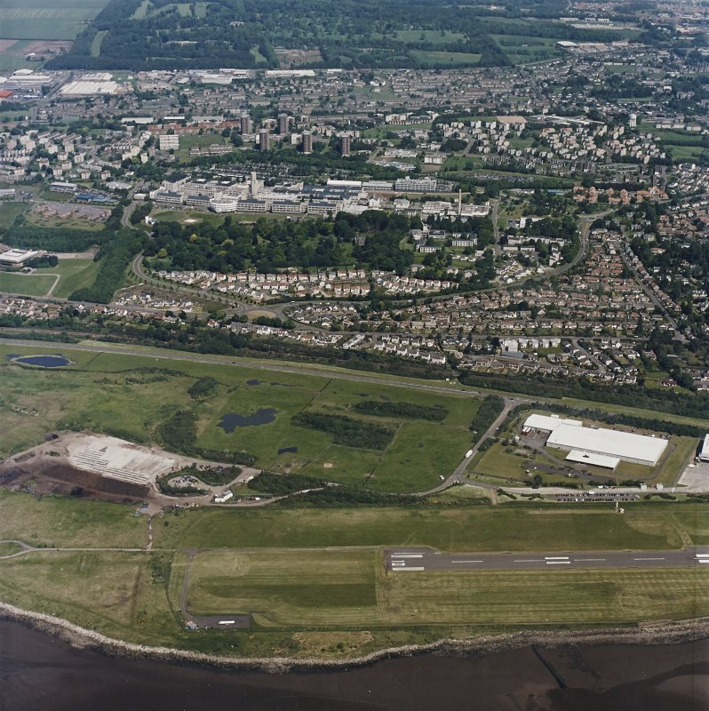 General oblique aerial view of Dundee centred on the hospital with the airport adjacent, taken from the S.