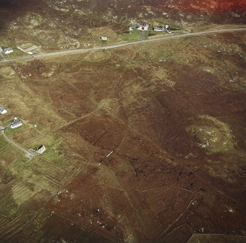 Oblique aerial view centred on the remains of the stone circles with lazy beds adjacent, taken from the SW.