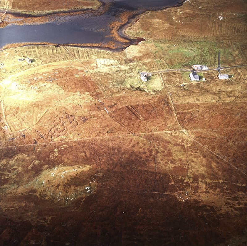 Oblique aerial view centred on the remains of the stone circles with the lazy beds adjacent, taken from the E.