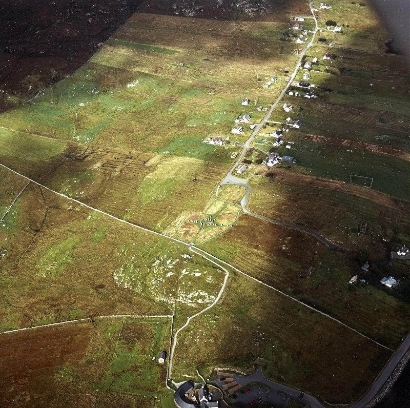 Oblique aerial view centred on the remains of the stone circle and stone alignments with the township and lazy beds adjacent, taken from the SSE.