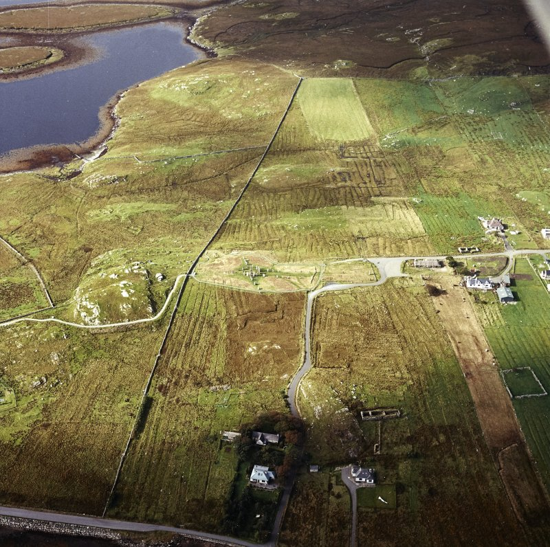 Oblique aerial view centred on the remains of the stone circle and stone alignments with the township and lazy beds adjacent, taken from the ESE.
