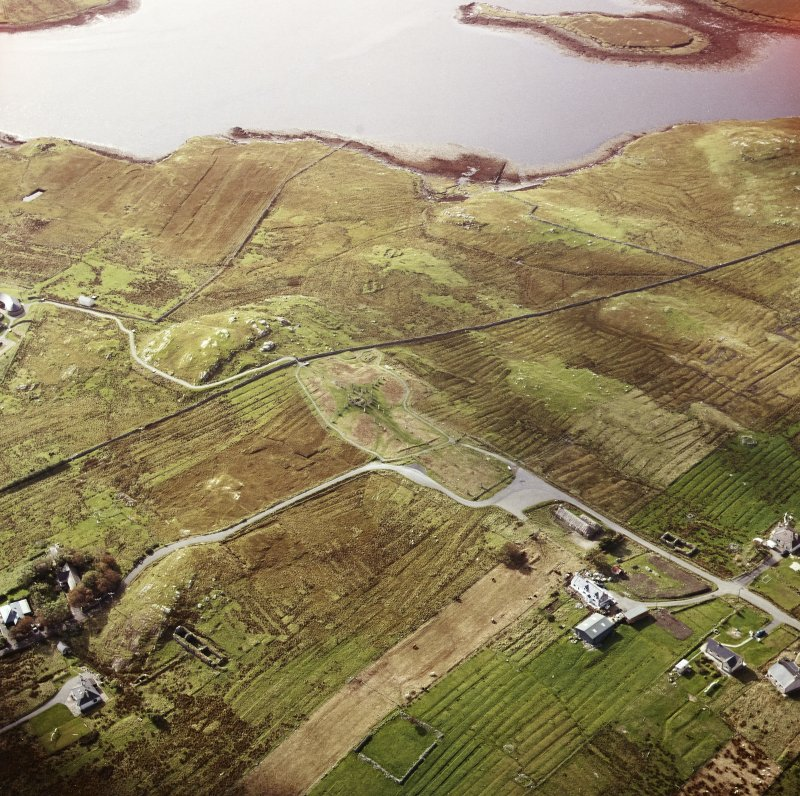 Oblique aerial view centred on the remains of the stone circle and stone alignments with the township and lazy beds adjacent, taken from the NE.
