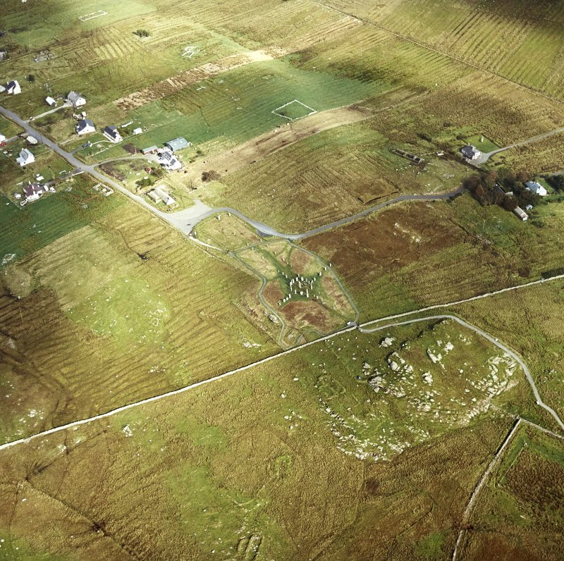 Oblique aerial view centred on the remains of the stone circle and stone alignments with the township and lazy beds adjacent, taken from the SW.