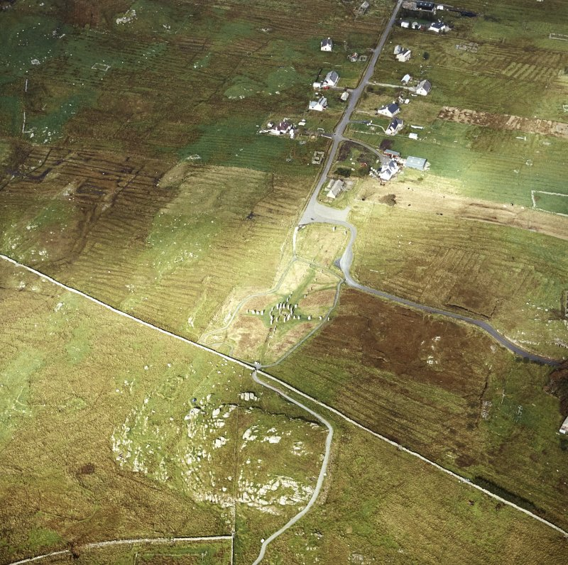 Oblique aerial view centred on the remains of the stone circle and stone alignments with the township and lazy beds adjacent, taken from the S.