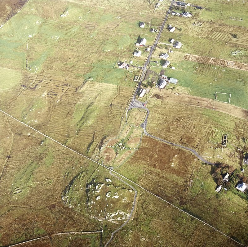 Oblique aerial view centred on the remains of the stone circle, chambered cairn and stone alignments with the township and lazy beds adjacent, taken from the S.