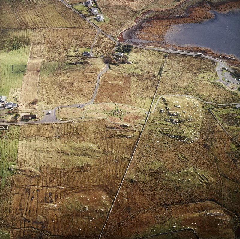 Oblique aerial view centred on the remains of the stone circle, chambered cairn and stone alignments with the township and lazy beds adjacent, taken from the W.
