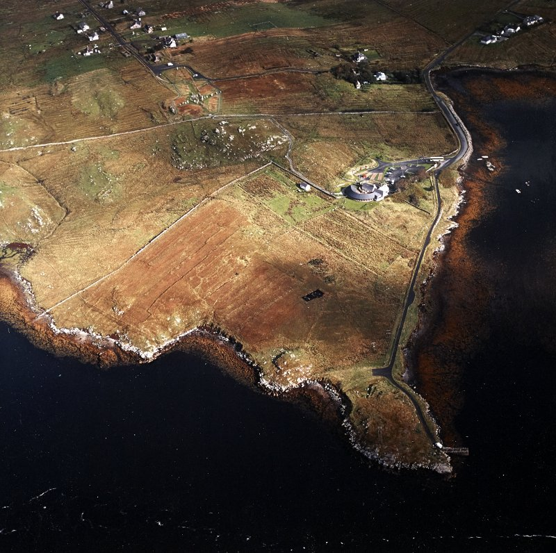 General oblique aerial view centred on the research centre, stone circle and stone alignments with the township adjacent, taken from the SW.