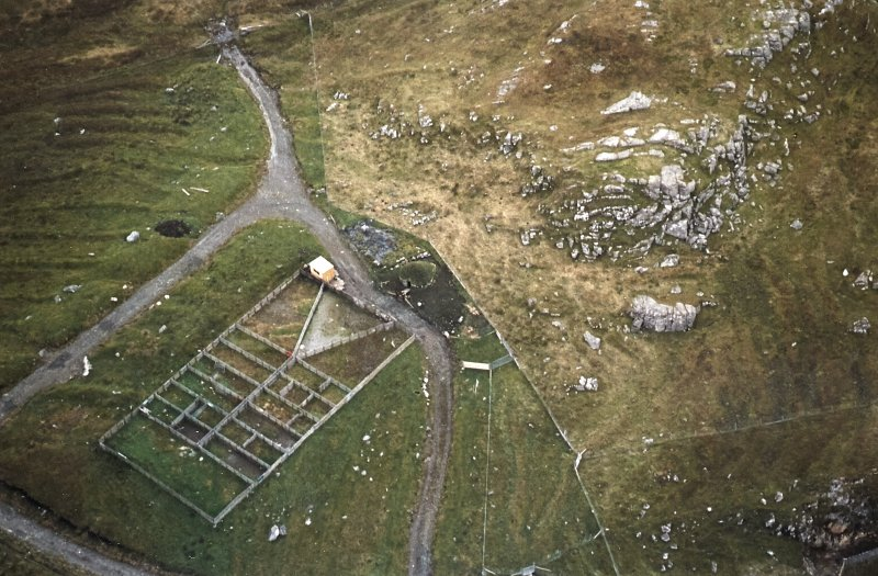 Oblique aerial view centred on the reconstructed shieling hut and sheep pen, taken from the NNW.