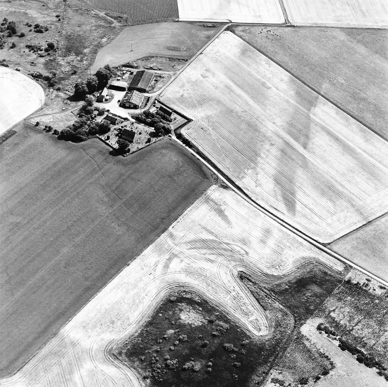 Gilchrist, oblique aerial view, taken from the NW, centred on the cropmarks of a promontory fort. Kilchrist Church is visible in the top left-hand corner of the photograph.
